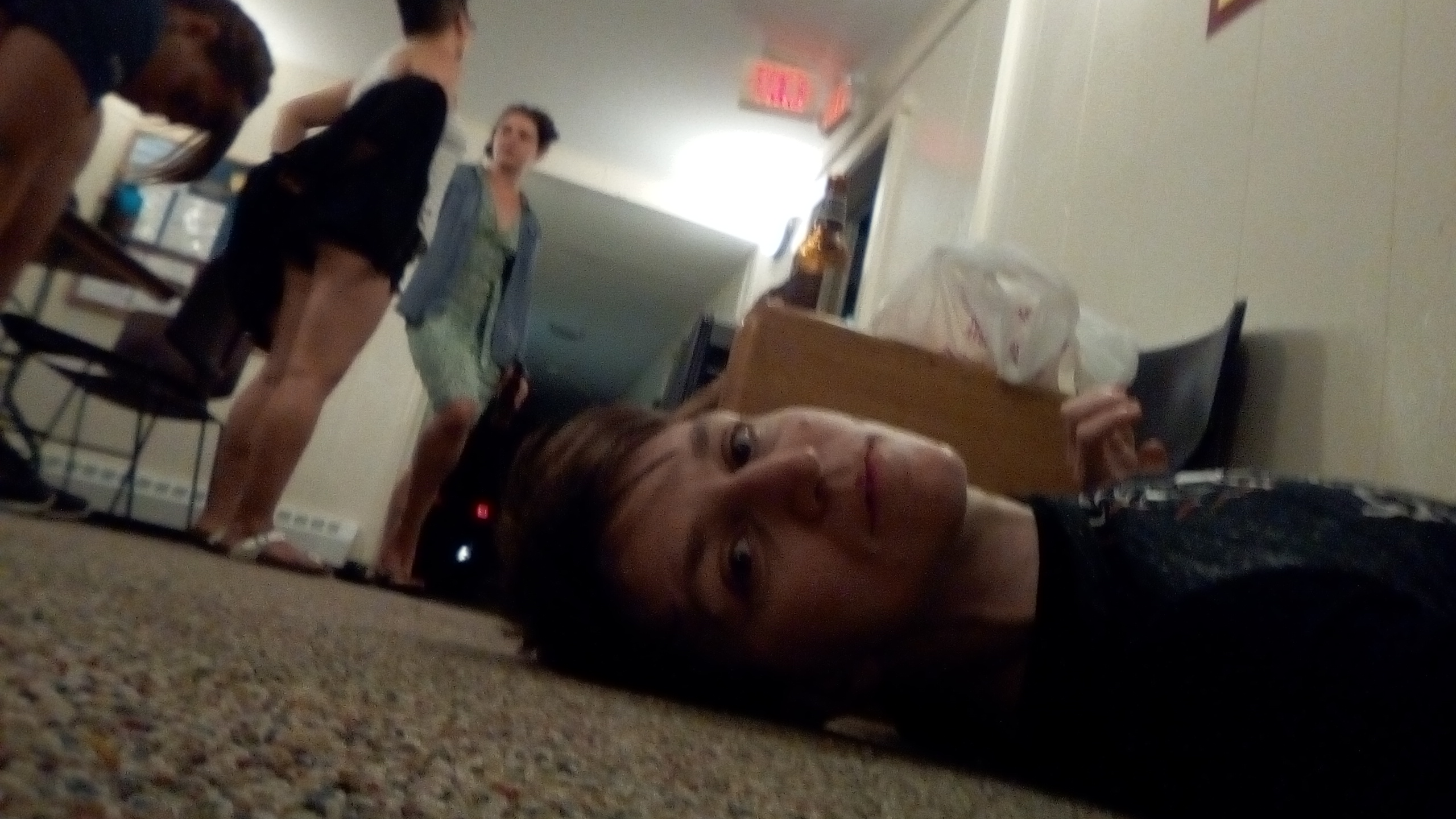 Asher lying on the floor of the dorms at the workshop with other students in the background.