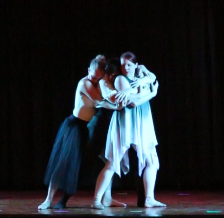 "A still image from the ballet ""Tenebrae""of three dancers in an embrace."