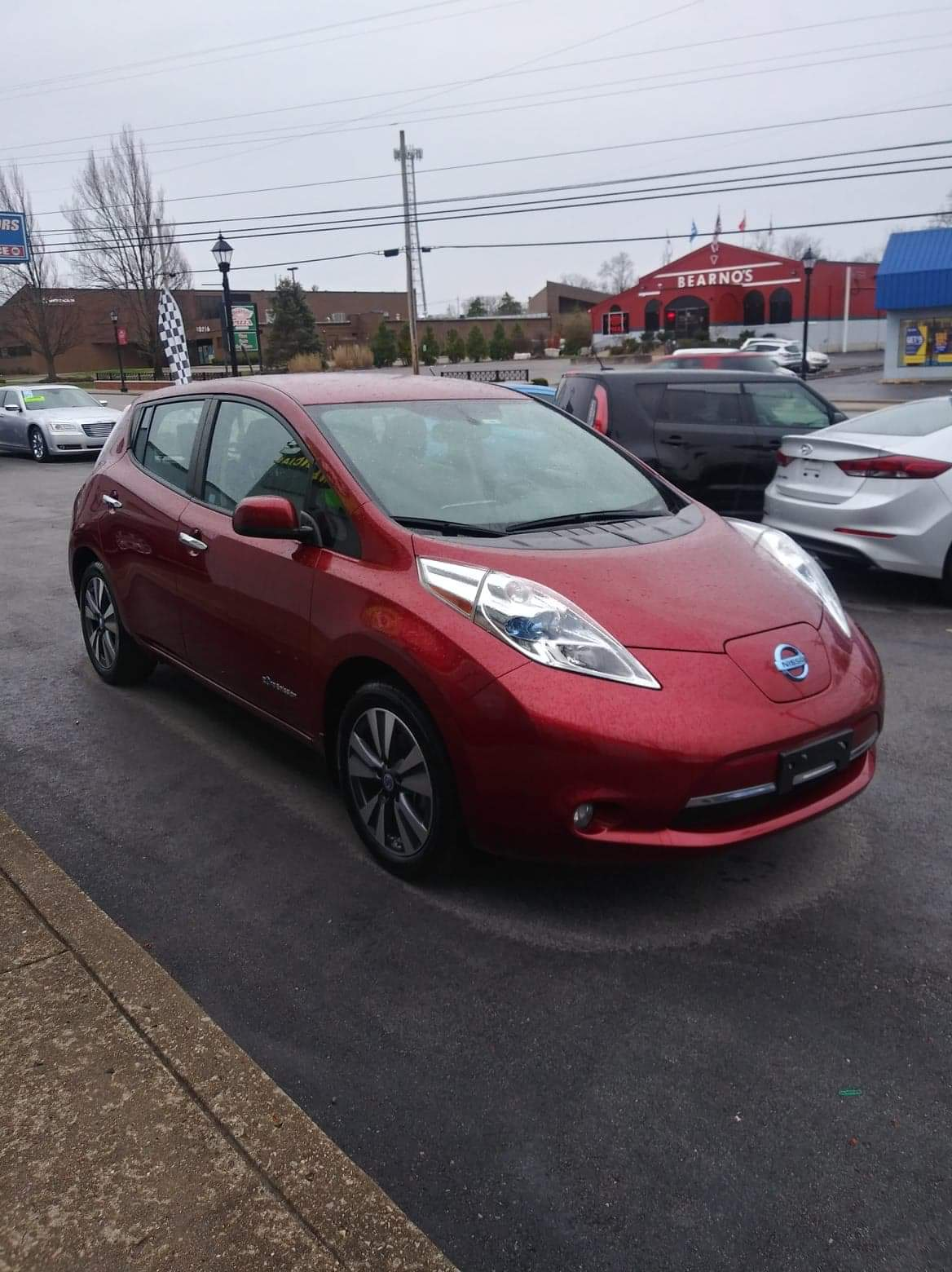 A red Nissan Leaf sits on the tarmac in front of a few other cars.