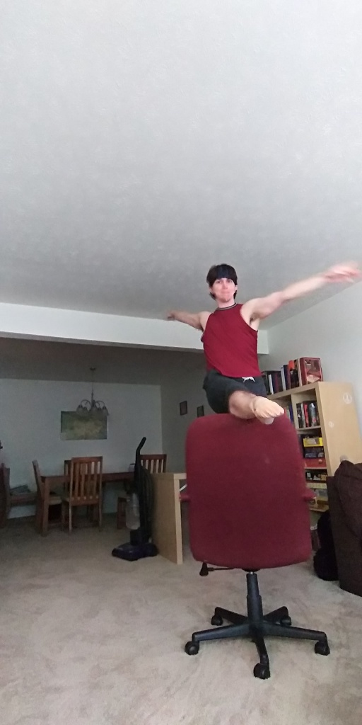 The author dancing in the living room of a shared apartment, with one leg atop the back of an office chair.