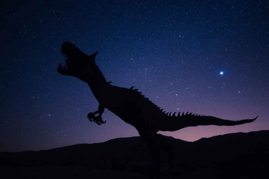 A carnivorous dinosaur silhouetted against a night sky.